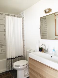 Bathroom 1 has a 2-faucet sink, dual flush toilet, and a shower/soaking tub.