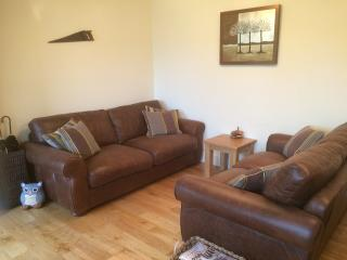 Guest Lounge, with big leather sofas and cushions.  Books, magazines and fruit is available here.