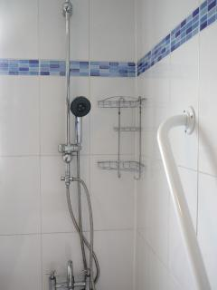 Tiled bathroom has a shower over the bath