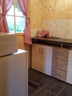 Küche mit Kühlschrank, Mikrowelle, Kaffeemaschine, Wasserkocher, Kochplatte mit Pfannen und Geschirr
