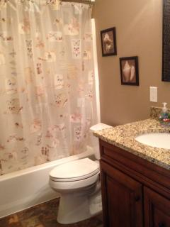 Full guest bathroom with tub/shower and granite countertop
