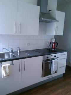 Kitchen with oven, hob, fridge. Separate utility room with washing machine & dishwasher, bread maker