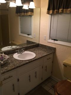bath with shower/tub combo and granite counters