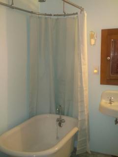The bathroom includes a vintage clawfoot tub.