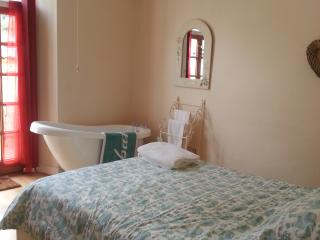 The bedroom with roll top bath and king size bed, with access through French doors to the garden