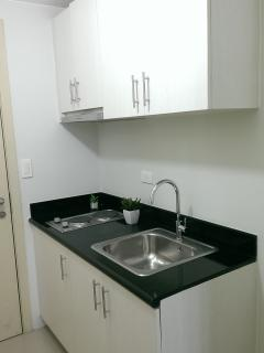 Washing basin and Cupboard storing cooking wares, cutlery and glasses