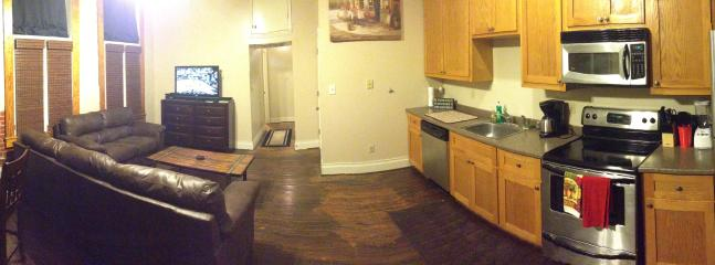 Panoramic view of the living room and kitchen area.