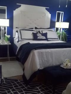 Customs bed with handmade headboard, designer 5-star bedding, standing mirrors and matching lamps.