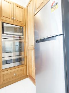 Kitchen features large fridge, oven, stove top, microwave, sandwich press, kettle and dishwasher.