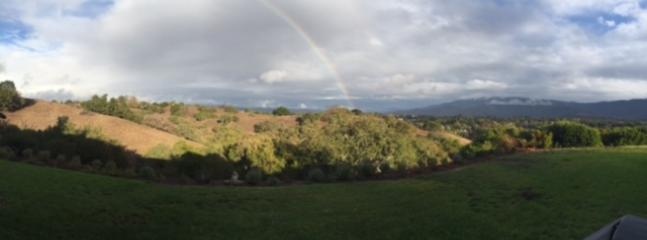 A rainbow over the backyard vista of mountains.