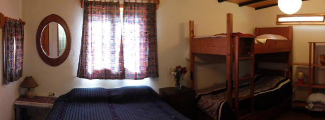bedroom with private bathroom, queen bed and bunks.
