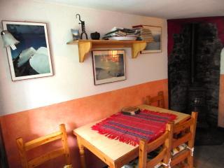 Tavolo con quattro sedie, sullo sfondo una bellissima stufa a legna antica