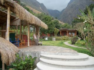 Mountain cloud forest to the rear of the property, thatched roof cabana at the lake's edge.