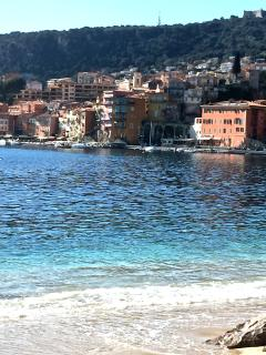 Looking back at the old town from the beach across the clear waters of the mediterranean