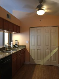 Kitchen with full size washer and dryer behind folding doors.