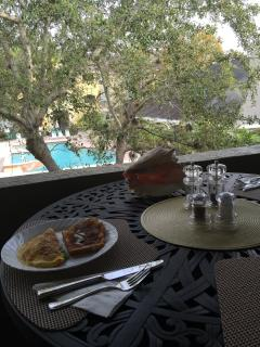 Enjoy a meal or a drink on the balcony overlooking the pool.