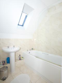 The large bathroom hasa a full size bath with shower over
