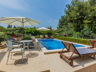 24 meter square swimming pool and sundeck area with sun loungers and umbrellas