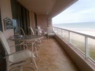 Angled view of the extra long, tiled balcony, facing the beach; view of beach is 180 degrees wide.