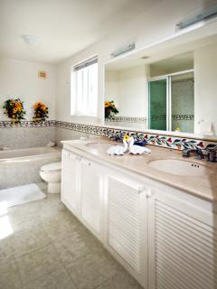 The main master bath has 2 sinks, tub and large shower with tiles seat