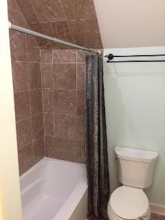 Shower with marble flooring and surrounds