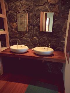 La salle de bain avec son mur en basalte  et sa douche en pierre naturelle.