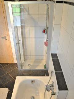 De badkamer is mooi uitgevoerd in wit/zwart en heeft een toilet, badkamermeubel, douchecabine en bad