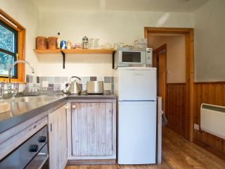 Kitchen with stainless steel worktop, ceramic hob, oven, microwave, friddge / freezer