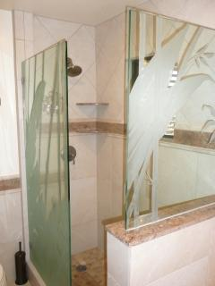 Beautiful walk-in shower with tropical etched glass and granite accents in the master bath