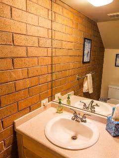 The half bath is located in the hall between the dining and living rooms.