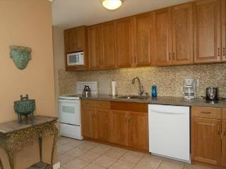 Fully renovated kitchen with beautiful cherry wood cabinets & granite countertops, view of Waikiki.