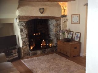 Ingle nook fireplace with log burner, original bare beams and stonework, high quality furnishings.