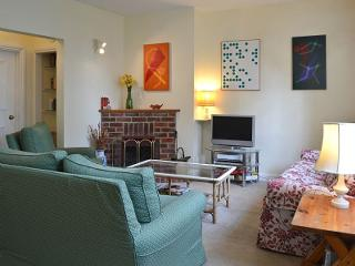 South facing sitting room with open fire, 3 and 2 seater sofas and armchair.