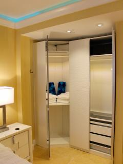 Dressing area with ample backlit closet space and full length mirror