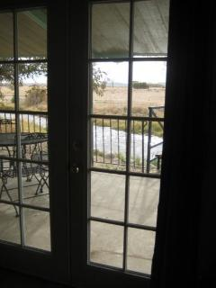 French doors lead out of the living room to a furnished patio looking over the creek.