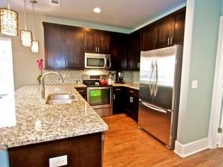 Kitchen is well appointed with granite and stainless steel appliances, and filled with warm natural light