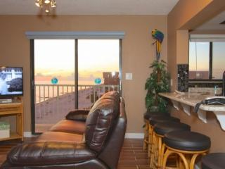 The living room has a view of the beach and extra bar stool dining