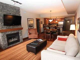 This spacious living area is features a cozy fireplace and a flat-screen TV.