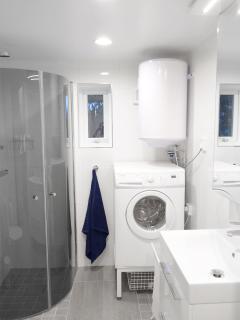 Bathroom with shower, washing machine / tumble dryer.