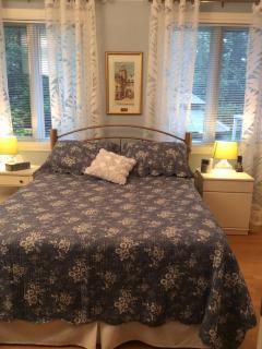 Chambre à l'étage avec lit queen, frigo et salle d'eau à proximité.