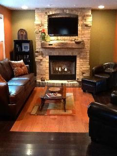 Living room is quaint with leather furniture, fireplace, antique sled coffee table -- cable & WiFi