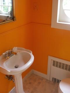 The cheery Powder room is just off the living room at the foot of the staircase.