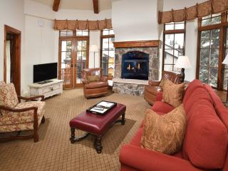 Penthouse living room with arched ceilings and rock face fireplace.