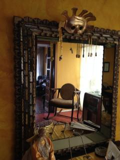Sala de estar, y estudio. Espejo antiguo de la Escuela Quiteña y Máscara del Sol El espejo madera.
