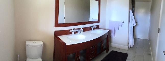 Dual sink in bathroom adjacent to guest bedroom.