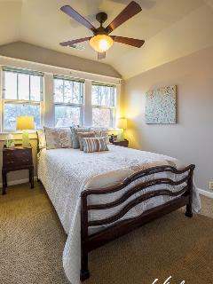 The smaller bedroom has a double bed with antique frame, two night stands, and a small closet.