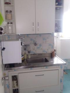 Cozinha com armários, pia, filtro elétrico com água gelada e normal