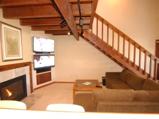 Large living room with dual HD TV entertainment wall and gas fireplace.