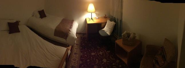 Habitación con un futón convertible en cama para dos personas, una cama indivudual y área de trabajo