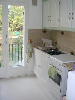Kitchen with river and lock views. Door onto balcony.